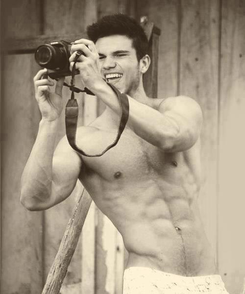 celeb taylor lautner with shirt off taking a photo with a camera and smiling
