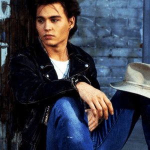 handsome actor johnny depp in leather jacket modeling with a hat on his knee