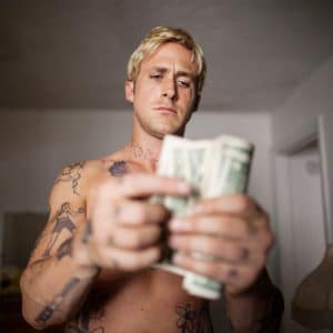 shirtless Ryan Gosling counts money with bleach blonde hair