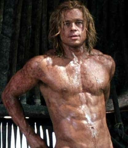 celebrity brad pitt with long hair showing off his 6 pack and all muddy