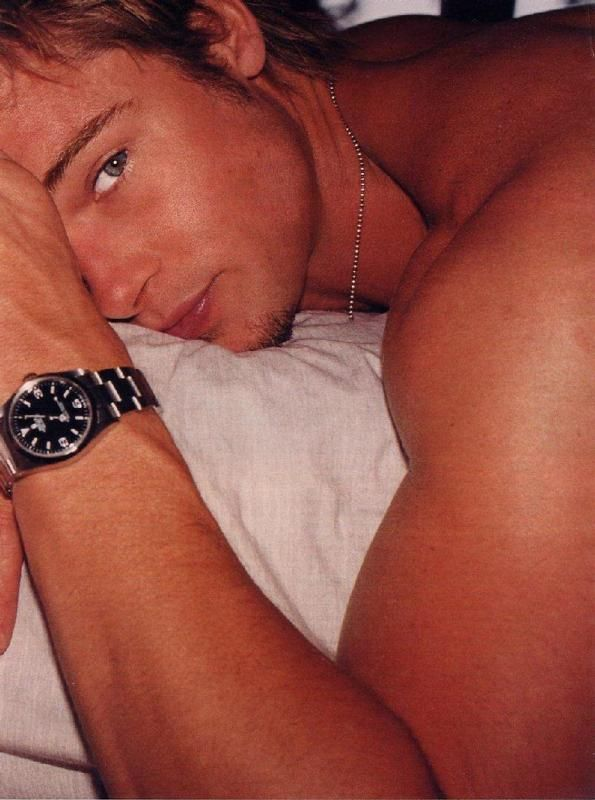 pic of actor brad pitt laying down showing off his muscular arms