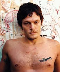 sexiest man alive norman reedus with shirt off and looking at the camera intensely