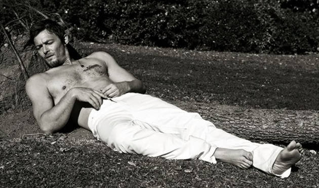 actor norman reedus with his shirt off laying on the ground black and white pic