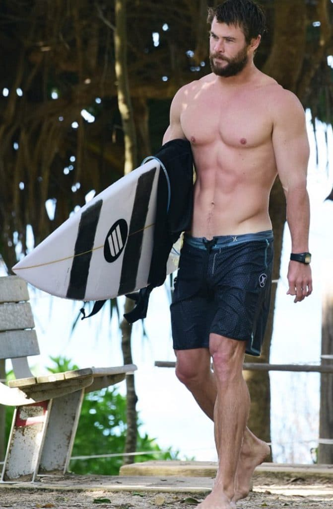 Chris Hemworth carrying his surfboard