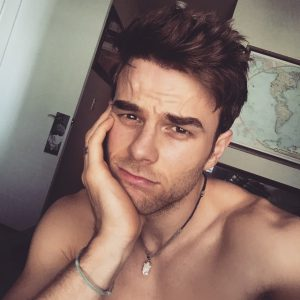 selfie pic of nathaniel buzolic with his hand on his chin