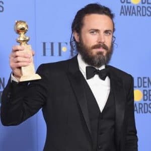 casey affleck holding up his golden globe award in suit and tie