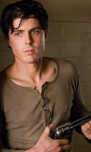 actor nominee casey affleck looking sexing in a tan shirt and holding a gun