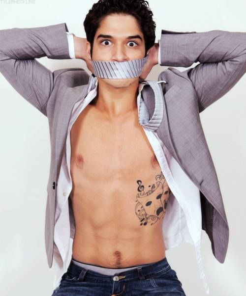 gorgeous man tyler posey with duck tape on his mouth and open shirt showing off his abs