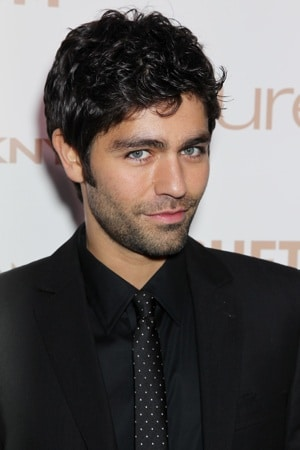 adrian grenier in a black suit tilting his head and looking well groomed