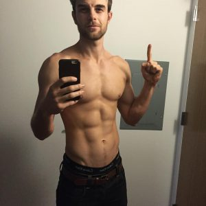 Nathaniel Buzolic taking a six pack selfie and pointing up