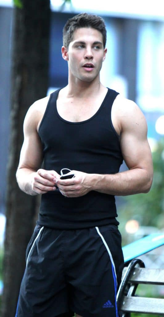 Dean Geyer with big muscles wearing black wife beater and shorts